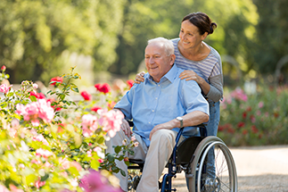 caregiver and man in wheelchair at the garden