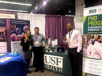 phd program representatives pose at their conference booth
