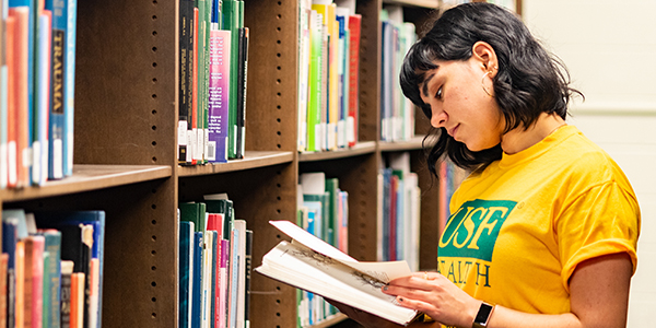 Health graduate student reads book in library