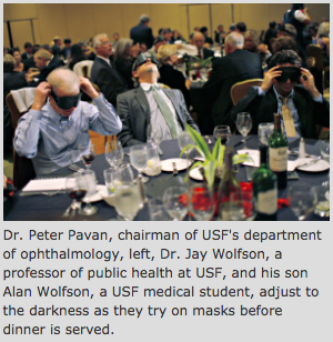 Dr. Peter Pavan, chairman of USF's department of ophthalmology, left, Dr. Jay Wolfson, a professor of public health at USF, and his son Alan Wolfson, a USF medical student, adjust to the darkness as they try on masks before dinner is served.